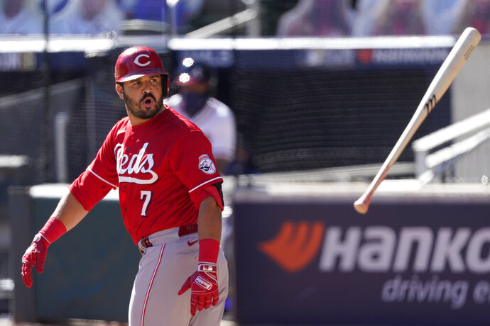 Cincinnati Reds third baseman Eugenio Suarez (7) tosses his bat after drawing a walk to load the bases in 11th inning during Game 1 of a National League wild-card baseball series against the Atlanta Braves, Wednesday, Sept. 30, 2020, in Atlanta. (AP Photo/John Bazemore)