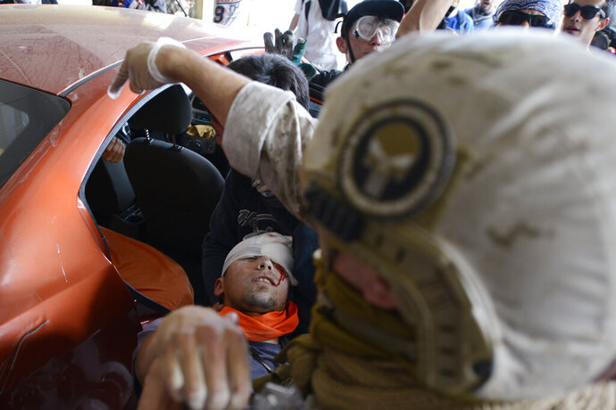 FILE - In this Oct. 25, 2019 file photo, an anti-government protester injured during clashes with police is placed into the backseat of a car in Valparaiso, Chile. In less than a month, more than 230 Chileans have lost sight in one eye, mostly due to the impact of pellets fired by the police during clashes with protesters demanding greater equality and improved social services. (AP Photo/Matias Delacroix, File)