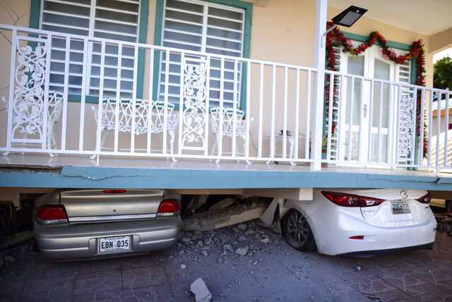 Cars are crushed under a home that collapsed after an earthquake hit Guanica, Puerto Rico, Monday, Jan. 6, 2020. A 5.8-magnitude quake hit Puerto Rico before dawn Monday, unleashing small landslides, causing power outages and severely cracking some homes. There were no immediate reports of casualties. (AP Photo/Carlos Giusti)