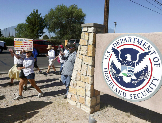 FILE - This June 2018 file photo shows protesters walking along Montana Avenue outside the El Paso Processing Center, in El Paso, Texas. On Tuesday, April 23, 2019, a U.S. government watchdog agency said they have launched an investigation in the wake of an Associated Press report revealing complaints about how immigration authorities treated hunger strikers at this facility. (Rudy Gutierrez/The El Paso Times via AP, File)