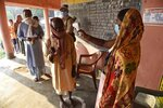 A woman wearing a face mask as a protective measure against the coronavirus screens the body temperature of voters at a polling station, during the first phase of state elections at Paliganj, in the eastern Indian state of Bihar, Wednesday, Oct. 28, 2020. With an overall declining coronavirus positive trend, Indian authorities decided to hold the first state legislature election since the outbreak of COVID-19. People began voting Wednesday in the country's third largest state Bihar with of a population of about 122 million people. (AP Photo/Aftab Alam Siddiqui)