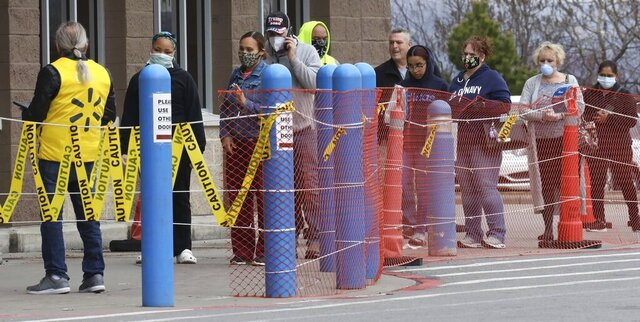 A line of shoppers wait for their chance to get into the Wilkes Barre Twp, Pa., Walmart, Saturday, April 4, 2020, as the business begins limiting the amount of customers allowed into the store as a result of the coronavirus outbreak. (Dave Scherbenco/The Citizens' Voice via AP)