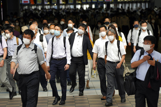 FILE - In this July 12, 2021, file commuters wearing face masks walk in a passageway during a rush hour at Shinagawa Station in Tokyo. Tokyo recorded 1,979 new COVID-19 cases Thursday, hitting a new six-month high one day before the Olympics are to begin amid growing worry about the worsening infections during the games. (AP Photo/Eugene Hoshiko, File)