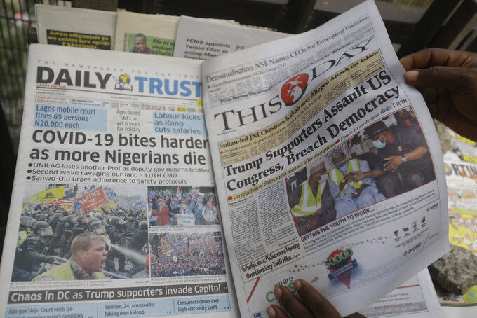 A man reads a newspaper reacting to the news of the assault on U.S Congress, in Lagos, Nigeria, Thursday Jan. 7, 2021.  New reports showing Police with gun drawn as protesters try to break into the House Chamber at the U.S. Capitol on Wednesday, in Washington, USA.(AP Photo/ Sunday Alamba)