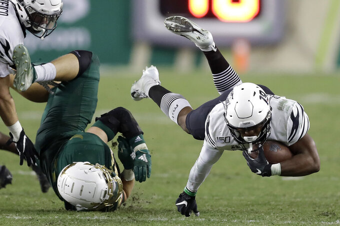 Memphis running back Kenneth Gainwell (19) gets upended by South Florida linebacker Andrew Mims during the second half of an NCAA college football game Saturday, Nov. 23, 2019, in Tampa, Fla. (AP Photo/Chris O'Meara)