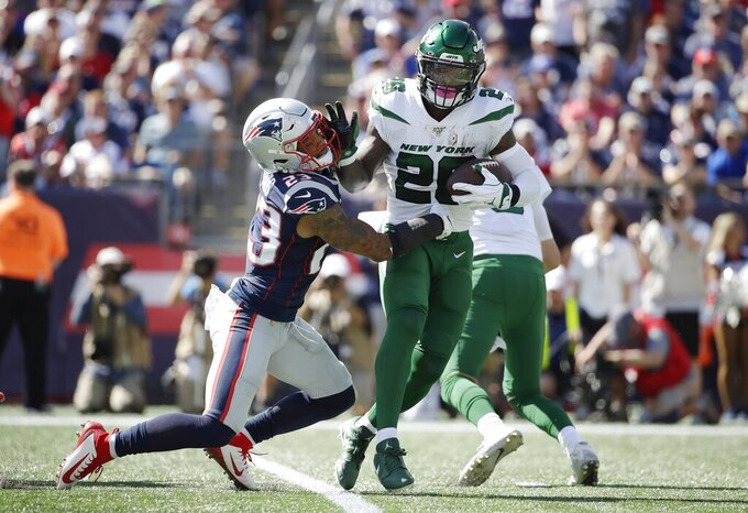 New York Jets running back Le'Veon Bell, right, tries to break free from the grasp of New England Patriots safety Patrick Chung in the first half of an NFL football game, Sunday, Sept. 22, 2019, in Foxborough, Mass. (AP Photo/Elise Amendola)