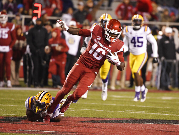 Arkansas receiver La'Michael Pettway is tripped up by LSU defender Terrence Alexander during the second half of an NCAA college football game, Saturday, Nov. 10, 2018, in Fayetteville, Ark. LSU won, 24-17. (AP Photo/Michael Woods)