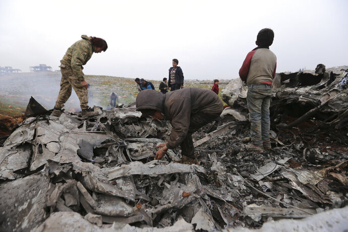 Syrians gather around a wreckage of a government military helicopter that was shot down in the countryside west of the city of Aleppo, Friday, Feb. 14, 2020. (AP Photo/Ghaith Alsayed)