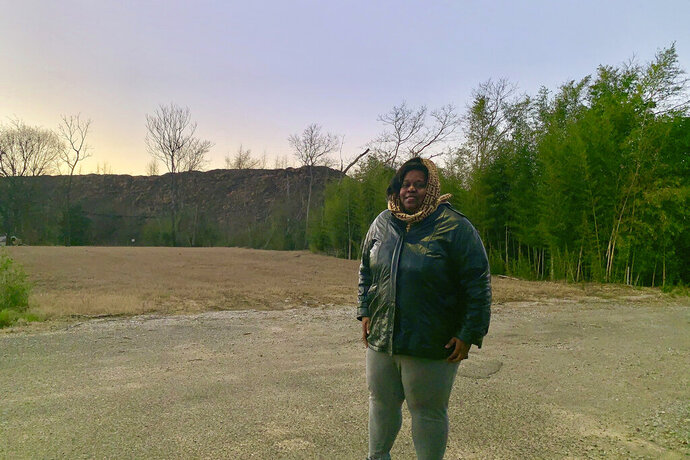 Keisha Brown, 40, stands in front of a scrap pile from one of the industrial properties that faces her house in a Superfund area in Birmingham, Ala., on Jan. 9, 2019. Brown said residents in the area have suffered for years from the effects of industrial pollution. The government shutdown has suspended federal cleanups at Superfund sites around the nation and forced the cancellation of public hearings, deepening the mistrust and resentment of surrounding residents who feel people in power long ago abandoned them to live among the toxic residue of the country's factories and mines. (AP Photo/Kimberly Chandler)