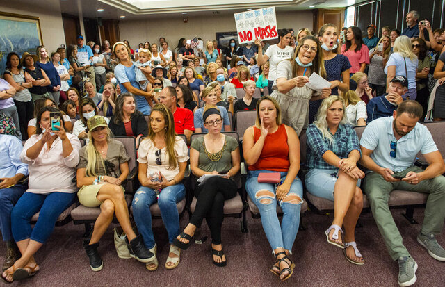 Angry residents react when the Utah County Commission meeting was adjourned before it even started, Wednesday, July 15, 2020, in Provo, Utah. The group protesting against face masks being required in schools removed the social distancing tape on the chairs and filled the Utah County Commission room to over flowing, prompting Commissioner Tanner Ainge to call for a vote to adjourn the meeting. (Rick Egan/The Salt Lake Tribune via AP)