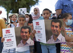 """Aws, 7, left, and Amr, 9, hold posters with a picture of their father, Mahmoud Nawajaa, a leading coordinator of the Palestinian-led boycott movement against Israel, BDS, during a protest calling for the EU to press for his release, in front of the German Representative Office, in the West Bank city of Ramallah, Tuesday, Aug. 11, 2020. The activist was arrested on July 30, remains in Israeli custody and has not been charged. Israel says the arrest is not connected to his boycott activities, and that he is is suspected of unspecified """"security offenses,"""