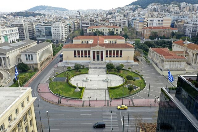 In this Wednesday, April 1, 2020 photo, an aerial view of the Athens University headquarters building and a deserted Panepistimiou street, in Athens. Deserted squares, padlocked parks, empty avenues where cars were once jammed bumper-to-bumper in heavy traffic. The Greek capital, like so many cities across the world, has seen its streets empty as part of a lockdown designed to stem the spread of the new coronavirus. (AP Photo/Thanassis Stavrakis)