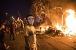 A masked anti-government protester stands by a burning barricade in Santiago, Chile, Monday, Oct. 28, 2019. Fresh protests and attacks on businesses erupted in Chile Monday despite President Sebastián Piñera's replacement of eight important Cabinet ministers with more centrist figures, and his attempts to assure the country that he had heard calls for greater equality and improved social services. (AP Photo/Rodrigo Abd)