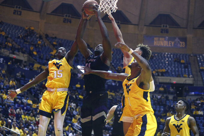 Kansas State forward Makol Mawien (14) grabs a rebound while defended by West Virginia forward Lamont West (15) during the first half of an NCAA college basketball game Monday, Feb. 18, 2019, in Morgantown, W.Va. (AP Photo/Raymond Thompson)