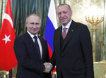 Russian President Vladimir Putin, left, shakes hands with Turkish President Recep Tayyip Erdogan during their meeting in the Kremlin in Moscow, Russia, Monday, April 8, 2019. Russian President Vladimir Putin is hosting his Turkish counterpart, Recep Tayyip Erdogan, for talks expected to focus on the situation in Syria and their two nations' booming economic ties. (Maxim Shipenkov/Pool Photo via AP)