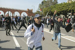 Protesting teachers run from security forces attempting to disperse a demonstration in Rabat, Morocco, Wednesday, Feb. 20, 2019. Moroccan police fired water cannons at protesting teachers who were marching toward a royal palace and beat people with truncheons amid demonstrations around the capital Wednesday. (AP Photo/Mosa'ab Elshamy)
