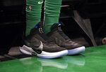In this Feb. 7, 2019 photo, Boston Celtics forward Jayson Tatum sits on the bench during an NBA basketball game against the Los Angeles Lakers in Boston. He is wearing Nike's latest performance basketball shoes, which from concept to reality, took about three years to put together. Or 30 years, depending on how you count. The Nike Adapt BB _ a self-lacing smart shoe that can be controlled by a smartphone _ gets released to the public on Sunday, Feb. 17, 2019, a date that just happens to coincide with the NBA All-Star Game in Charlotte. It has a motor embedded within the shoe, and a hefty $350 price tag. It has a motor embedded within the shoe, and a hefty $350 price tag. (AP Photo/Elise Amendola)