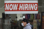 FILE - This May 7, 2020, file photo shows a man wearing a mask while walking under a Now Hiring sign at a CVS Pharmacy during the coronavirus outbreak in San Francisco.  Friday, Dec. 4, monthly U.S. jobs report will help answer a key question hanging over the economy: Just how much damage is being caused by the resurgent coronavirus, the resulting restrictions on businesses and the reluctance of consumers to shop, travel and dine out?  (AP Photo/Jeff Chiu, File)