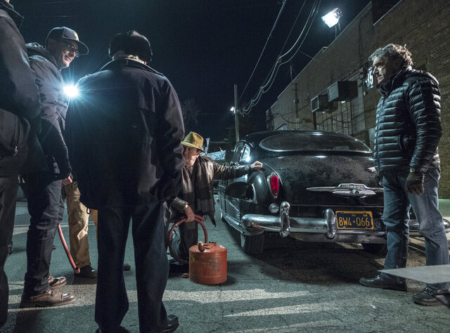 This image released by Netflix shows Robert De Niro, kneeling center, on the set of