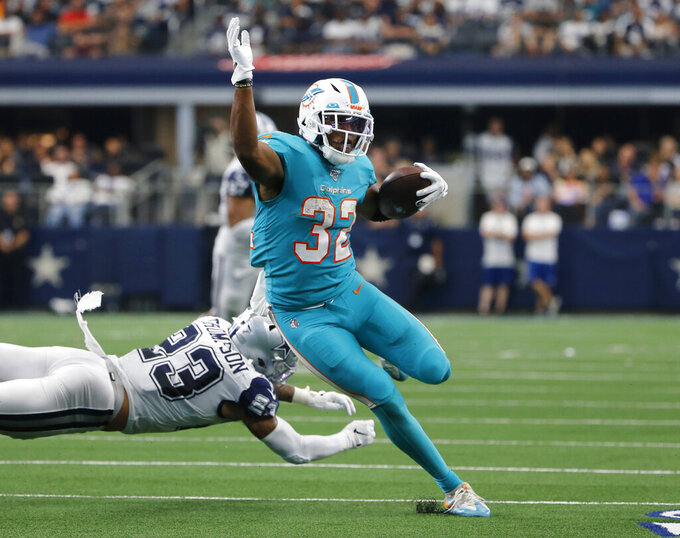 Miami Dolphins running back Kenyan Drake (32) escapes a tackle attempt by Dallas Cowboys defensive back Darian Thompson (23) in the first half of an NFL football game in Arlington, Texas, Sunday, Sept. 22, 2019. (AP Photo/Michael Ainsworth)