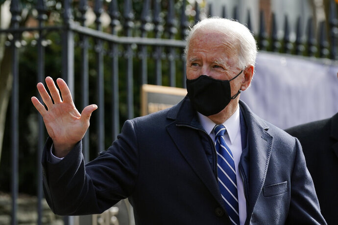 President Joe Biden waves as he departs after attending Mass at Holy Trinity Catholic Church, Sunday, Jan. 24, 2021, in the Georgetown neighborhood of Washington. Biden plans to sign an executive order Monday, Jan. 25 that aims to boost government purchases from U.S. manufacturers. (AP Photo/Patrick Semansky)