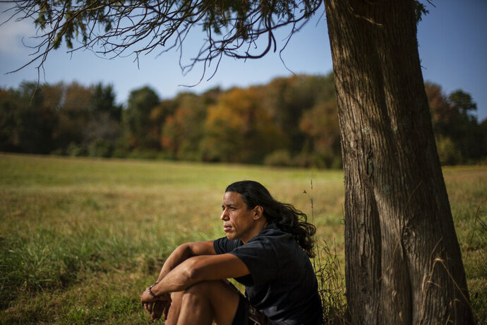 Annawon Weeden, 46, a member of the Mashpee Wampanoag Tribe, sits for a portrait outside his home in Oakdale, Conn., Friday, Sept. 25, 2020.