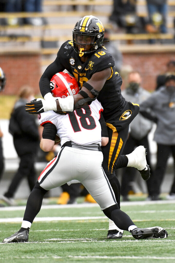 Missouri defensive lineman Trajan Jeffcoat, top, sacks Georgia quarterback JT Daniels during the first half of an NCAA college football game Saturday, Dec. 12, 2020, in Columbia, Mo. (AP Photo/L.G. Patterson)