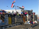Anti-government protesters sit-in on barriers set up by security forces to close the Sinak bridge leading to the Green Zone government areas during ongoing protests, in Baghdad, Iraq, Sunday, Nov. 17, 2019. (AP Photo/Khalid Mohammed)