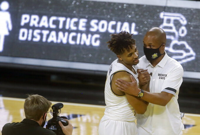 Interim Wichita State head coach Isaac Brown, right, congratulates Tyson Etienne after Etienne scored 26 points in a 85-50 win over Oral Roberts Wednesday, Dec. 2, 2020 in Wichita, Kan. (Travis Heying/The Wichita Eagle via AP)