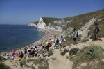 People make their way to Durdle Door Beach, as the public are being reminded to practice social distancing following the relaxation of coronavirus lockdown restrictions, near Lulworth in Dorset, England, Saturday, May 30, 2020.  (Andrew Matthews/PA via AP)