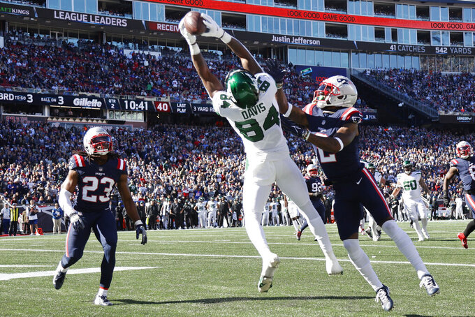 New York Jets wide receiver Corey Davis (84) grabs a touchdown pass while covered by New England Patriots cornerback Jalen Mills, right, during the first half of an NFL football game, Sunday, Oct. 24, 2021, in Foxborough, Mass. At left is New England Patriots defensive back Kyle Dugger (23). (AP Photo/Mary Schwalm)