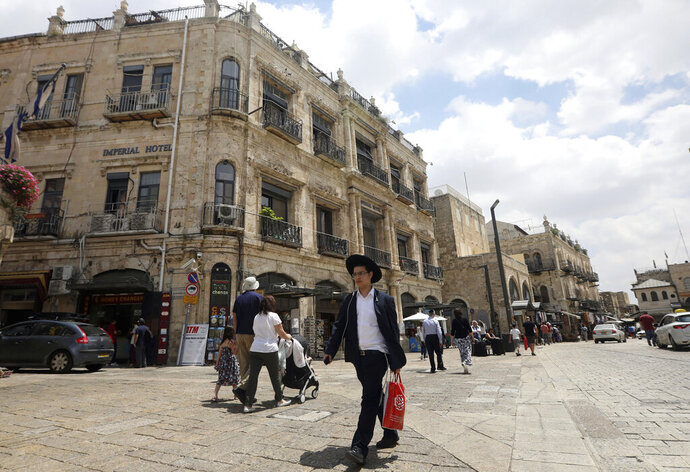 People walk past the Palestinian-run Imperial Hotel, that was part of a legal battle, in Jerusalem's Old City, Thursday, June 13, 2019. Israel's Supreme Court has ruled against the Greek Orthodox Church in a long-running legal battle over the sale of three properties in predominantly Palestinian parts of Jerusalem's Old City to a Jewish settler group. (AP Photo/Mahmoud Illean)