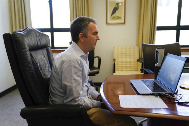 In this image provided by the Office of the Governor of Virginia,  Virginia Gov. Ralph Northam as he participates in a Skype interview from his office at the Capitol in Richmond, Va., Thursday April 2, 2020. (Jack Mayer/Office of the Governor of Virginia via AP)