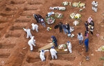 Cemetery workers in protective clothing bury victims of the new coronavirus at the Vila Formosa cemetery in Sao Paulo, Brazil, Wednesday, July 15, 2020. Brazil is nearing 2 million cases of COVID-19 and 75,000 deaths. (AP Photo/Andre Penner)