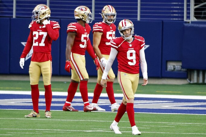 San Francisco 49ers place kicker Robbie Gould (9) is followed to the bench by Dontae Johnson (27), Azeez Al-Shaair (51) and Joe Walker (59) after Gould attempted an onside kick that Dallas Cowboys wide receiver CeeDee Lamb returned for a touchdown in the second half of an NFL football game in Arlington, Texas, Sunday, Dec. 20, 2020. (AP Photo/Michael Ainsworth)