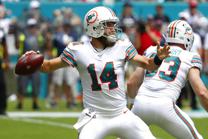 FILE - In this Sept. 15, 2019, file photo, Miami Dolphins quarterback Ryan Fitzpatrick (14) looks to pass during the first half at an NFL football game against the New England Patriots, in Miami Gardens, Fla. Ryan Fitzpatrick will start at quarterback Sunday for the winless Miami Dolphins at Buffalo, and Josh Rosen will be back on the bench. Coach Brian Flores announced the decision Wednesday, Oct. 16, 2019. (AP Photo/Wilfredo Lee, File)