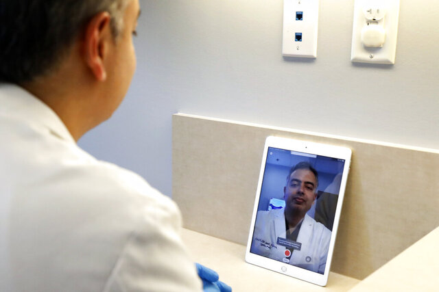 Dermatologist Dr. Seemal Desai poses for a photo in an examination room in his office in Plano, Texas, Thursday, May 7, 2020. Desai uses the privacy of an examination room and a tablet computer to virtually visit with some of his patients. (AP Photo/Tony Gutierrez)