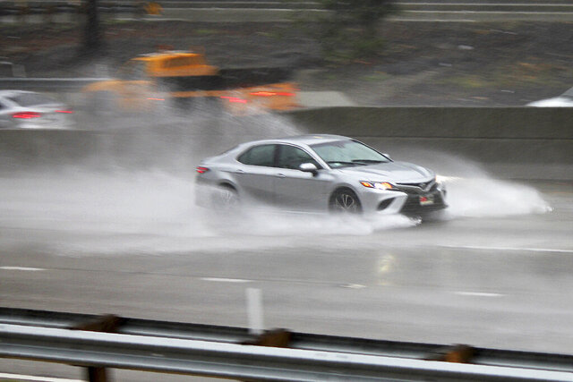 A car on the northbound Harbor Freeway (I-110) in downtown Los Angeles plows through deep water during a torrential downpour on Monday, April 6, 2020. Snow and rain fell Monday on California as spring delivered the kind of stormy weather that was missing most of the winter. Numerous spinouts were reported on Los Angeles-area freeways, and there were scattered reports of roadway flooding and canyon road rockfalls. (AP Photo/John Antczak)