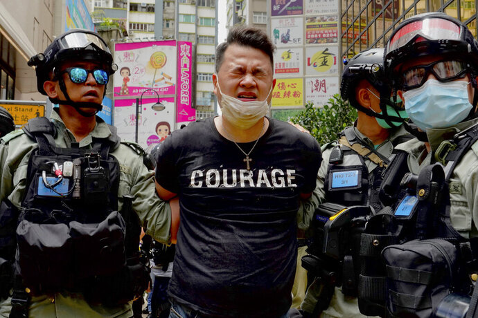 Police detain a protester after spraying pepper spray during a protest in Causeway Bay before the annual handover march in Hong Kong, Wednesday, July. 1, 2020. Hong Kong marked the 23rd anniversary of its handover to China in 1997, and just one day after China enacted a national security law that cracks down on protests in the territory. (AP Photo/Vincent Yu)