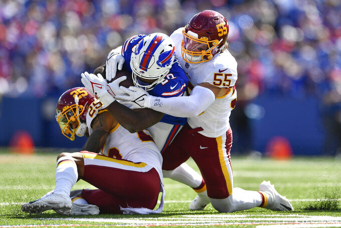 Washington Football Team's Cole Holcomb (55) and Benjamin St-Juste (25) tackle Buffalo Bills' Zack Moss (20) during the first half of an NFL football game Sunday, Sept. 26, 2021, in Orchard Park, N.Y. (AP Photo/Adrian Kraus)
