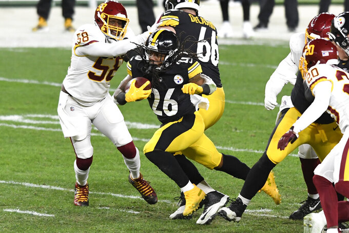 Pittsburgh Steelers running back Anthony McFarland (26) carries the ball past Washington Football Team outside linebacker Thomas Davis (58) during the first half of an NFL football game in Pittsburgh, Monday, Dec. 7, 2020. (AP Photo/Barry Reeger)
