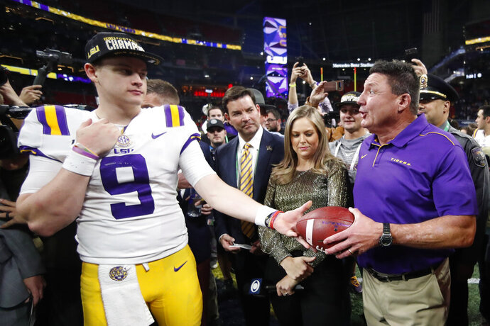 LSU quarterback Joe Burrow and LSU head coach Ed Orgeron celebrate after the Southeastern Conference championship NCAA college football game against Georgia, Saturday, Dec. 7, 2019, in Atlanta. LSU won 37-10. (AP Photo/John Bazemore)
