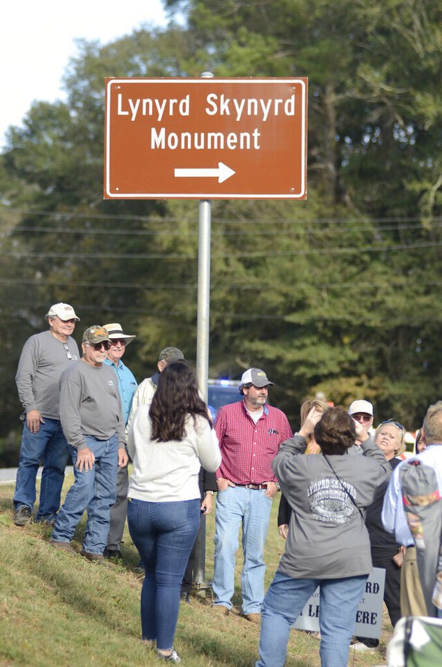 Fans and monument organizers gather at newly dedicated highway signs for the Lynyrd Skynyrd Monument near the site of the band's Oct. 20, 1977, plane crash in Gillsburg, Miss., Sunday, Nov. 15, 2020. Fans gathered Sunday as the Mississippi Department of Transportation unveiled exit signs from Interstate 55 near McComb and state Highway 568 near Gillsburg, the Enterprise-Journal reported. (Matt Williamson/The Enterprise-Journal via AP)