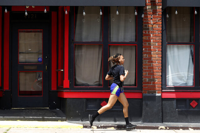 FILE - In this Thursday, May 7, 2020, file photo, a person jogs past a closed nightclub in St. Louis. Running is seeing an increase in participation since the coronavirus outbreak began taking off in the United States. (AP Photo/Jeff Roberson, File)
