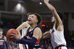 Pepperdine guard Colbey Ross, left, drives to the basket while pressured by Gonzaga guard Ryan Woolridge during the first half of an NCAA college basketball game in Spokane, Wash., Saturday, Jan. 4, 2020. (AP Photo/Young Kwak)