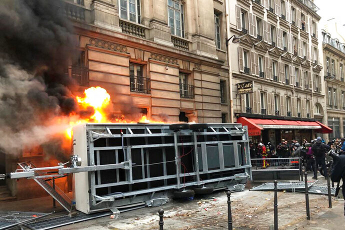 A truck is set ablaze during a demonstration in Paris, Thursday, Dec. 5, 2019. The Eiffel Tower shut down Thursday, France's vaunted high-speed trains stood still and teachers walked off the job as unions launched nationwide strikes and protests over the government's plan to overhaul the retirement system. (AP Photo/Alexander Turnbull)