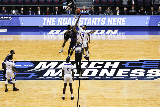 FILE - In this March 19, 2019, file photo, Fairleigh Dickinson's Kaleb Bishop (12) and Prairie View A&M's Iwin Ellis (13) leap for the opening tip-off in the first half of a First Four game of the NCAA college basketball tournament in Dayton, Ohio. NCAA President Mark Emmert says NCAA Division I basketball tournament games will be played without fans in the arenas because of concerns about the spread of coronavirus. (AP Photo/John Minchillo, File)