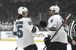 San Jose Sharks defenseman Erik Karlsson, left, is congratulated by left wing Evander Kane (9) after Karlsson scored in the first period of an NHL hockey game against the Los Angeles Kings, Monday, Nov. 25, 2019, in Los Angeles. (AP Photo/Michael Owen Baker)