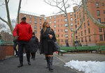 In this March 6, 2019 photo, Lynne Patton, right, HUD executive, and Robert Madison, left, associate director of community organization Jacob Riis Settlement, tour Queensbridge Houses residencies in New York. Patton has spent the past month living with tenants in New York City public housing complexes. She says she wanted to shine a spotlight on public housing ills such as mold and heat and hot water outages by spending a week at a time in four different complexes run by the New York City Housing Authority. (AP Photo/Bebeto Matthews)