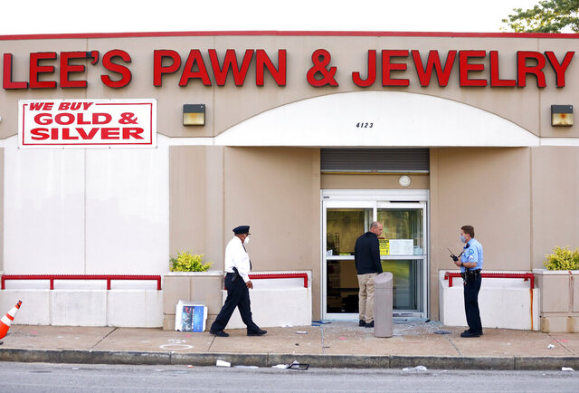 Police investigate the scene of a shooting at Lee's Pawn & Jewelry in St. Louis, Tuesday, June 2, 2020. A 77-year-old retired St. Louis police officer who served 38 years on the force was shot and killed by looters at the pawn shop early Tuesday, police said. David Dorn was found dead on the sidewalk in front of Lee's Pawn & Jewelry, which had been ransacked after peaceful protests over the death of George Floyd turned violent overnight. (David Carson/St. Louis Post-Dispatch via AP)